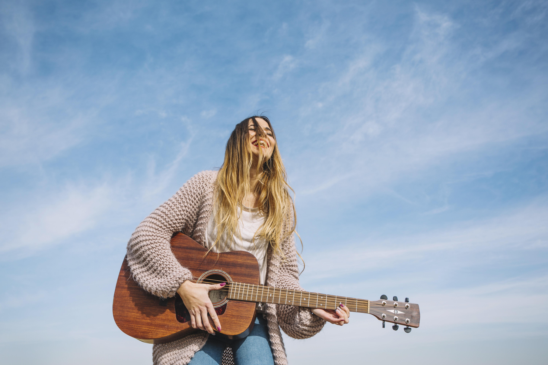 爽やかにギターを弾く少女の画像