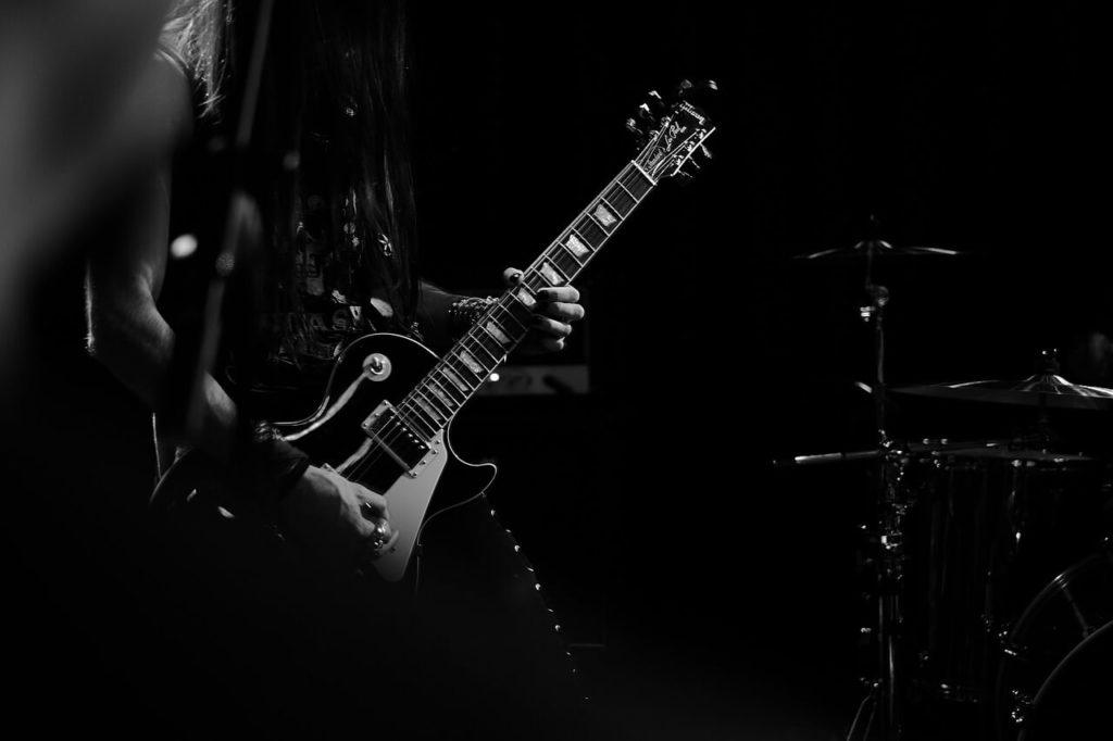 暗闇でギターを弾く画像